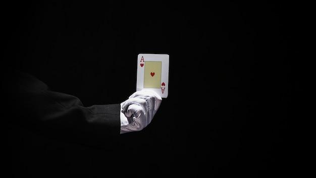 Hand des zauberers, die spielkarte der asse gegen schwarzen hintergrund hält