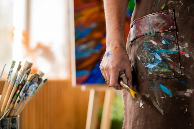 Hand des zeitgenössischen künstlers in der schürze, die pinsel hält, während er in seinem eigenen kunststudio arbeitet