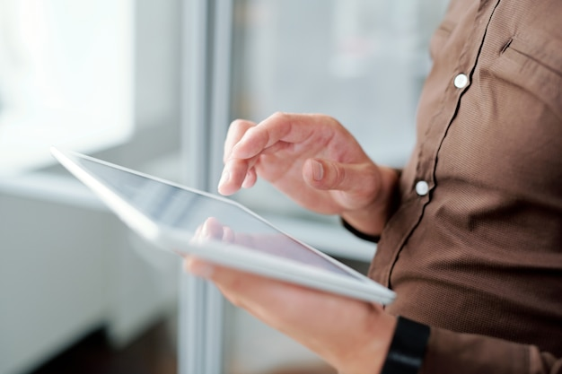 Hand des zeitgenössischen mobilen geschäftsmannes über anzeige des digitalen tablets beim scrollen durch online-informationen