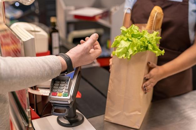 Hand des zeitgenössischen reifen männlichen verbrauchers mit smartwatch über bildschirm des zahlungsautomaten, der durch kassiererzähler im supermarkt steht
