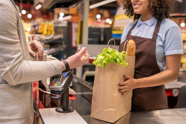 Hand des zeitgenössischen reifen mannes mit smartwatch, die handgelenk über zahlmaschine hält, während an der registrierkasse im supermarkt steht