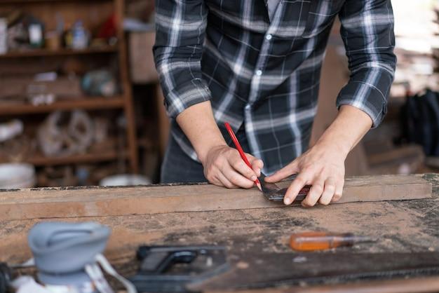 Hand des zimmermanns, der einen bleistift und ein lineal verwendet, um auf dem holzbrett zu messen, um die holzarbeiten in der tischlerei zu erledigen.
