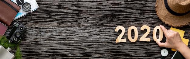 Hand, die 2020 guten rutsch ins neue jahr-zahl auf hölzernen tisch mit abenteuerzusatz-einzelteilfahne setzt