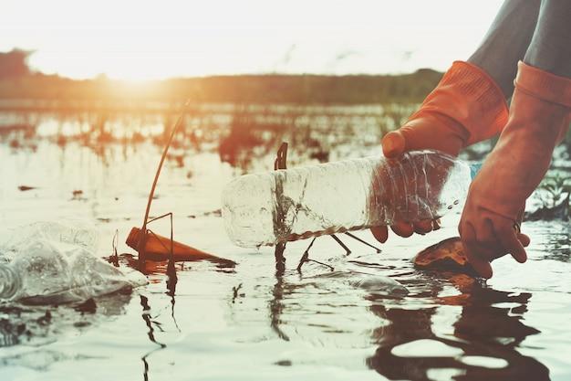 Hand, die abfallplastik für das säubern in fluss aufhebt
