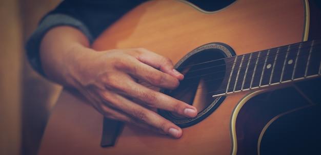 Hand, die akustische gitarre spielt