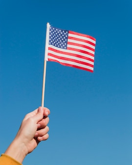 Hand, die amerikanische flagge auf blauem himmel hält