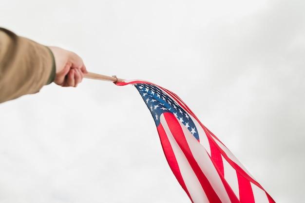 Hand, die amerikanische flagge im himmel wellenartig bewegt