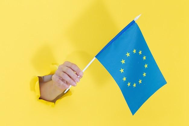 Hand, die amerikanische flagge vom gelben zerrissenen papier hält. europa. konzept