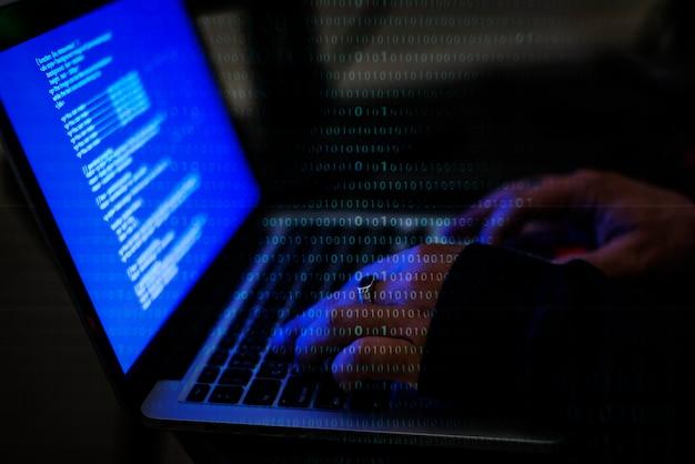 Hand, die an computerlaptop des blauen bildschirms arbeitet