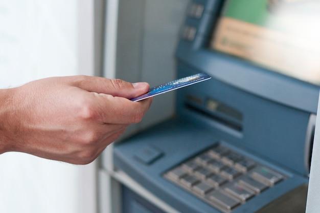 Hand, die atm-karte in bankmaschine einfügt, um geld zurückzuziehen. geschäftsmann männer hand setzt kreditkarte in geldautomaten