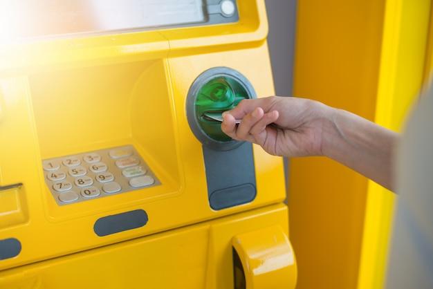 Hand, die atm-karte in bankomat einsetzt, um geld abzuheben.