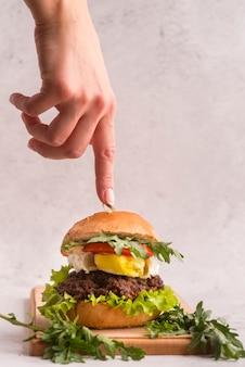 Hand, die auf einen köstlichen hamburger zeigt