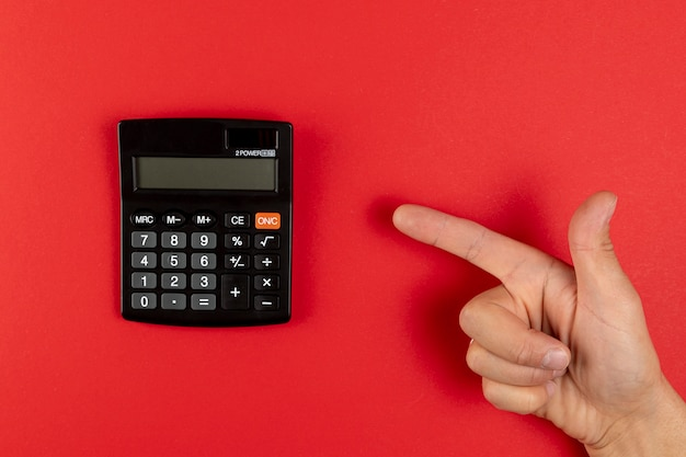 Hand, die auf einen minitaschenrechner zeigt