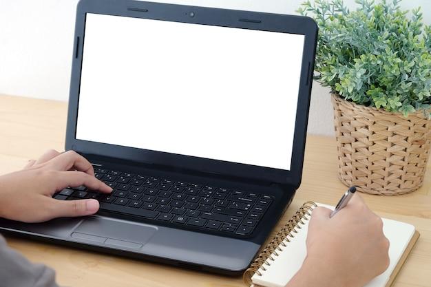 Hand, die auf laptop mit leerem bildschirm schreibt und auf notizbuch schreibt