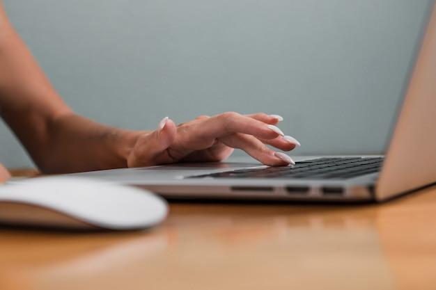 Hand, die auf laptoptastatur schreibt