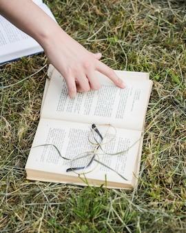 Hand, die auf offenes buch auf gras zeigt