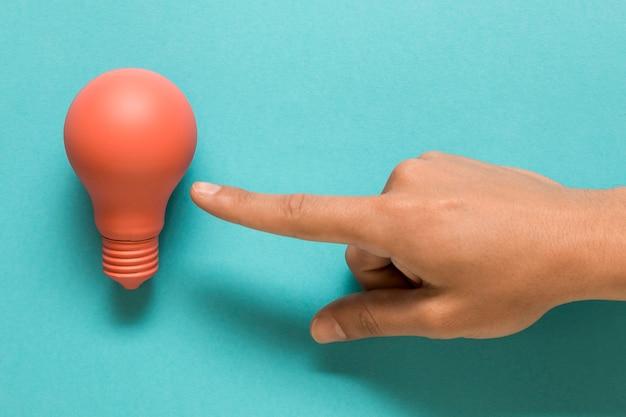 Hand, die auf rosa lampe auf farbiger oberfläche darstellt