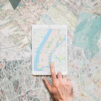 Hand, die auf tablette mit karte klopft