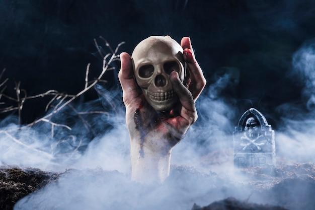 Hand, die aus dem boden heraus haftet und schädel hält