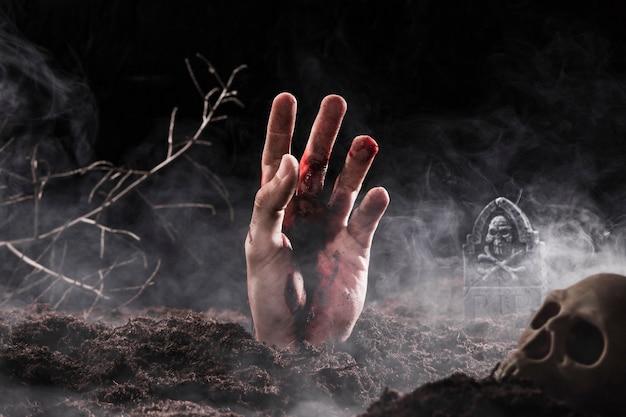 Hand, die aus dem boden heraus im nebel haftet