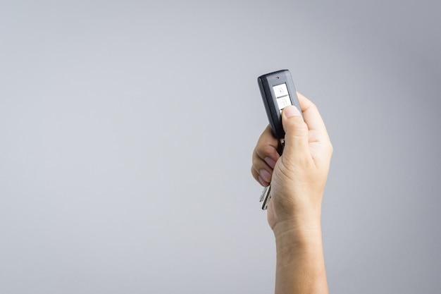 Hand, die autofernbedienung hält und drückt
