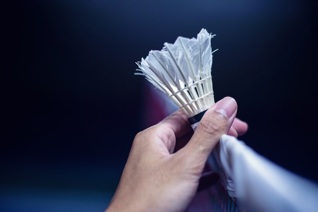 Hand, die badminton über dem netz hält