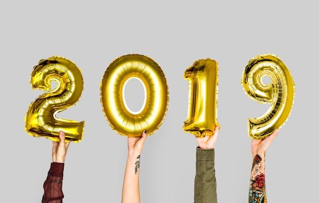 Hand, die ballon des neuen jahres 2019 hält