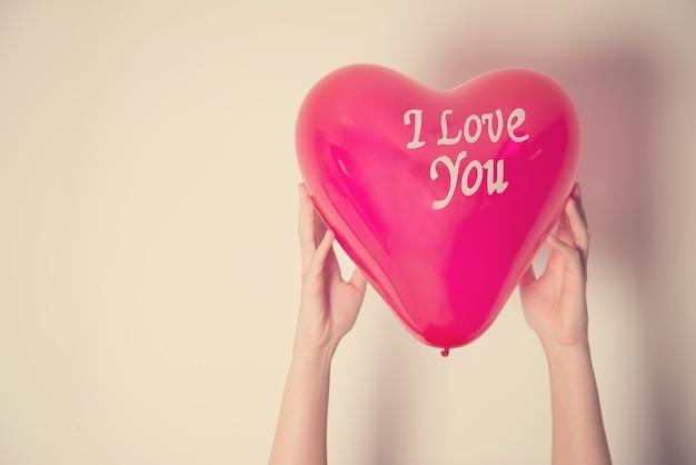 Hand, die ballon und text ich liebe dich mit retro- filtereffekt hält