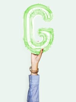Hand, die ballonbuchstabe g hält
