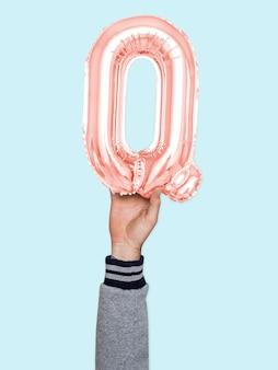 Hand, die ballonbuchstaben q hält