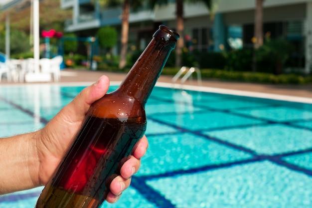 Hand, die bierflasche am pool hält