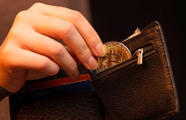 Hand, die bitcoin in seine brieftasche auf schwarzem hintergrund nah oben setzt.