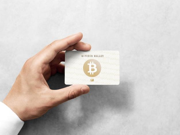 Hand, die bitcoin-karte mit geprägtem goldenem logo hält