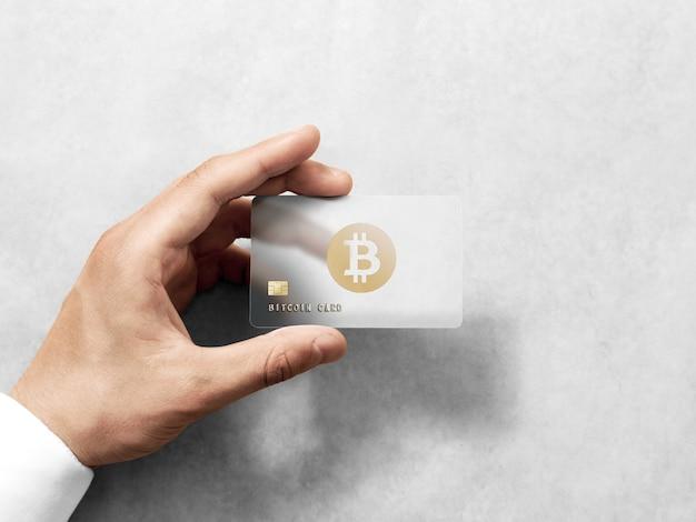Hand, die bitcoin-kartenschablone mit geprägtem goldlogo hält