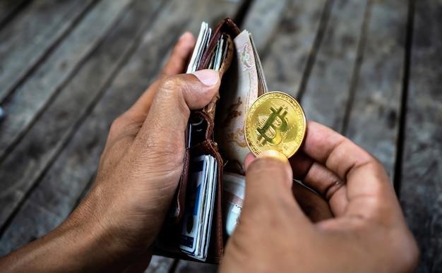Hand, die bitcoin-münze mit geldbörse hält