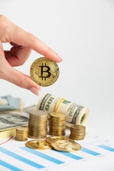 Hand, die bitcoin über münzenstapel hält