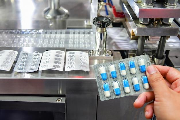 Hand, die blaue kapselpackung an der produktionslinie für medizinpillen hält industrielles pharmazeutisches konzept