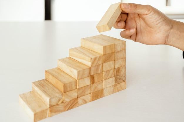 Hand, die blockholzspielkonzept hält risiko des managements und strategieplanwachstumsgeschäftsteamwork