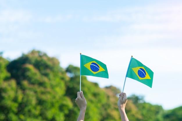Hand, die brasilien-flagge auf hintergrund des blauen himmels hält. unabhängigkeitstag im september und fröhliche feierkonzepte