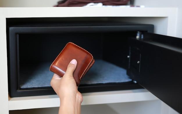 Hand, die braune geldbörse in einem sicheren kasten hält.