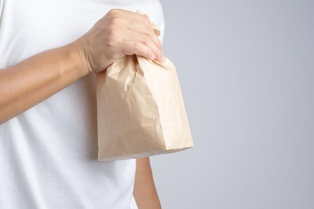 Hand, die braune papiertüte des krümels hält