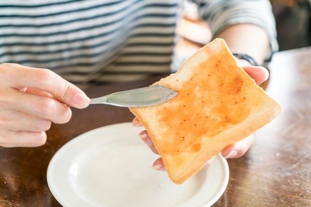 Hand, die brot und erdbeermarmelade macht zum frühstück hält
