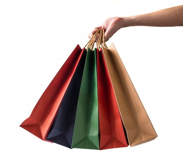 Hand, die bunte papiereinkaufstaschen auf weißem hintergrund hält