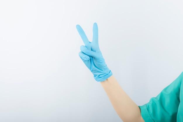 Hand, die chirurgischen handschuh trägt und siegesgeste zeigt.