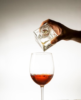 Hand, die cognac in ein glas auf einem hellen hintergrund gießt