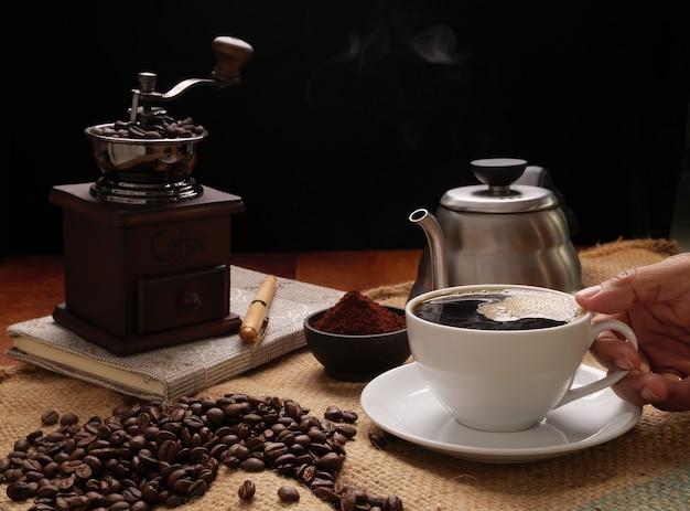 Hand, die dampfkaffeetasse mit mühle, gerösteten bohnen, kaffeepulver und kessel über sackleinenhessisch auf schmutzholz-tischhintergrund gießt