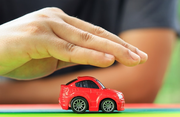 Hand, die das auto schützt und das auto versichert sicheres reisekonzept
