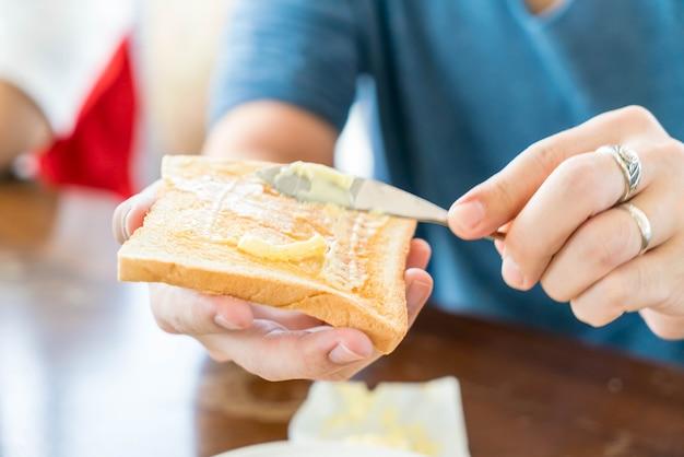 Hand, die das brot und butterherstellung zum frühstück hält