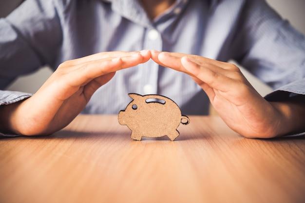 Hand, die das ikonensparschwein - der versicherung für ablagerung schützt