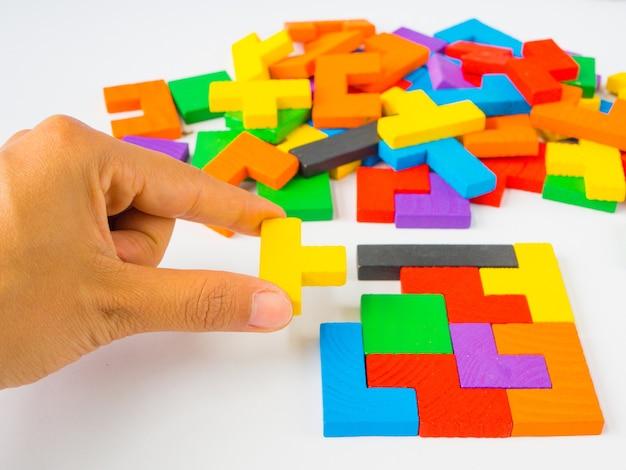 Hand, die das letzte stück hält, um ein quadratisches tangrampuzzlespiel abzuschließen